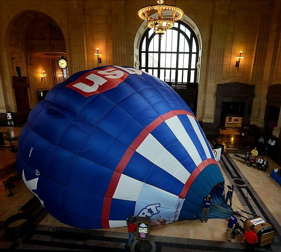Organizers of the U.S. Bank Great Midwest Balloon Festival kick off the Balloon Festival Charity Race Challenge by partially inflating the U.S. Bank's full-sized, hot air balloon Wednesday morning at Union Station in Kansas City, Mo. Sponsors, volunteers, organizers and representatives of local charities participating in the challenge will gather to kick-off discount ticket sales benefitting and exclusively available only through participating charitable organizations. The festival, which will feature 60 balloons, will be held August 9-10. (AP Photo/The Kansas City Star, Rich Sugg) Photo: Rich Sugg, Associated Press