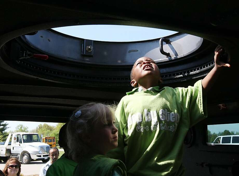The sixth annual BIG Truck Day was held Wednesday May 8, 2013, in Glazebrook Park in Godfrey, Ill. Children from Step By Step Day Care in Brighton, Ill., check out the gun turret opening in the top of the Madison County Sheriff's Department's tactical response truck which was part of the display. Many trucks were on display ranging from delivery vehicles to construction equipment and emergency vehicles. Children were bused into the park from local schools to tour the big trucks. (AP Photo/The Telegraph, John Badman)  THE NEWS-DEMOCRAT AND THE POST-DISPATCH OUT Photo: John Badman, Associated Press