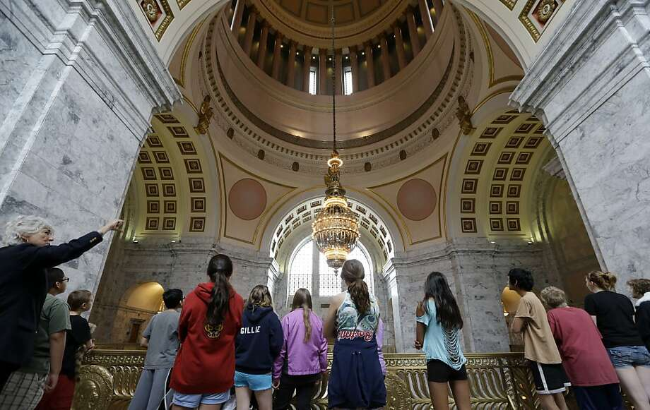 Capitol tour guide Laurie Maricle, left, leads a group of middle school children from Bellingham, Wash., as they look up toward the dome Wednesday, May 8, 2013,  in Olympia, Wash. Lawmakers completed their regular session on April 28 and are scheduled to return for a special legislative session Monday in order to complete a new state budget. (AP Photo/Elaine Thompson) Photo: Elaine Thompson, Associated Press