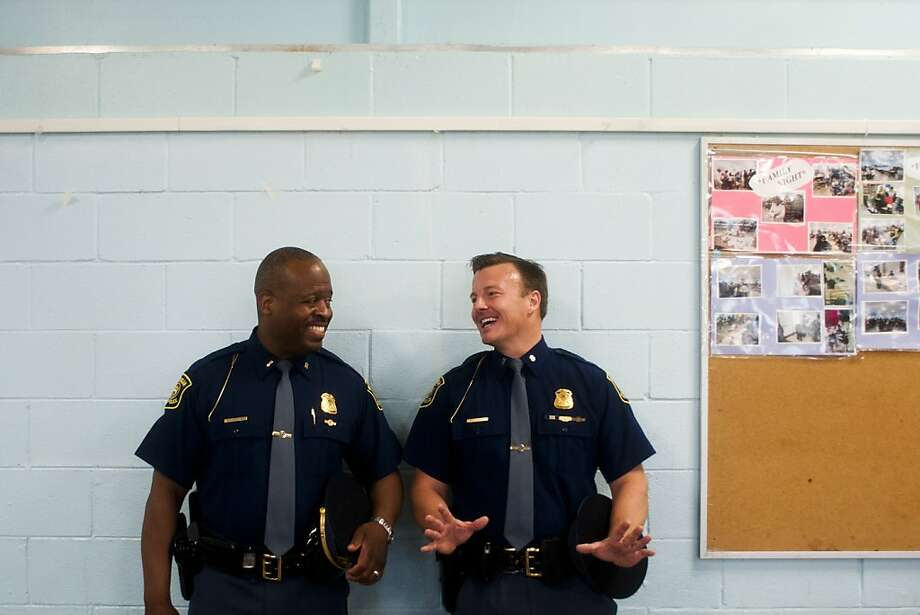Lt. Brian K. Cole, Sr., left, Michigan State Police Flint post's public information officer, laughs as he listens to First Lt. Gabriel Covey, based in Lansing, after the two spoke with young students in the cafeteria on Wednesday, May 8, 2013 at Bryant Elementary School as nearly two dozen Michigan state troopers gathered to kick off the state police's Teaching, Educating and Mentoring program at the city's schools. (AP Photo/The Flint Journal, Zack Wittman) LOCAL TV OUT; LOCAL INTERNET OUT Photo: Zack Wittman, Associated Press