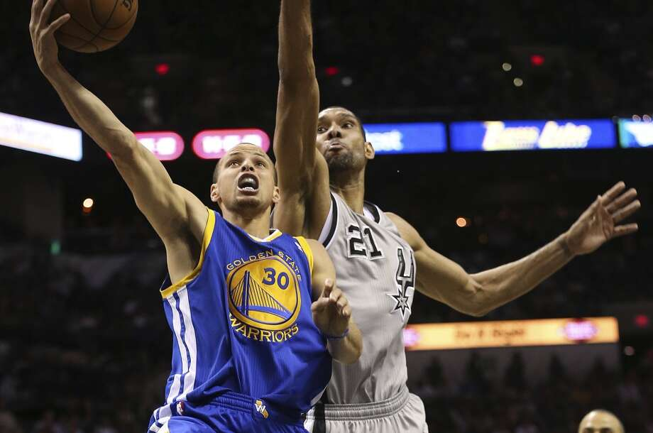Golden State Warriors' Stephen Curry scores as San Antonio Spurs' Tim Duncan defends during the second half of Game 2 in the NBA Western Conference semifinals at the AT&T Center, Wednesday, May 8, 2013. The Warriors won, 100-91 to even the series at 1-1.