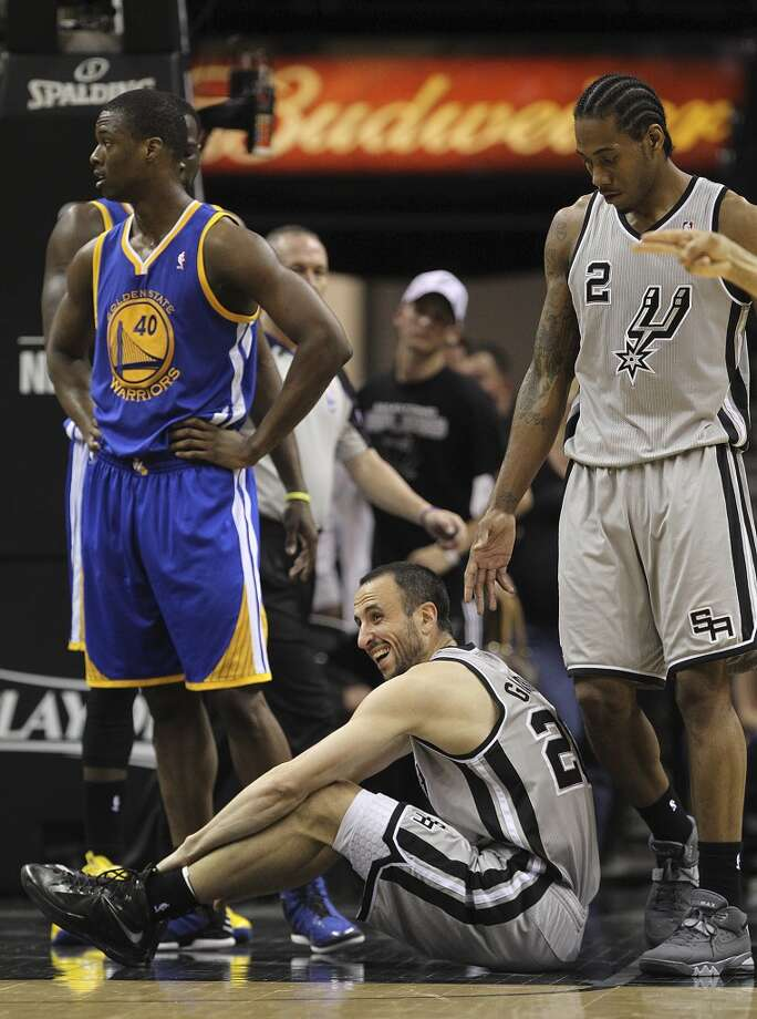 San Antonio Spurs' Manu Ginobili sits on the court after he was fouled during the second half of Game 2 in the NBA Western Conference semifinals  against the Golden State Warriorsat the AT&T Center, Wednesday, May 8, 2013. The Warriors won, 100-91 to even the series at 1-1. Next to Ginobili is Kawhi Leonard, right, and Golden State Warriors' Harrison Barnes.