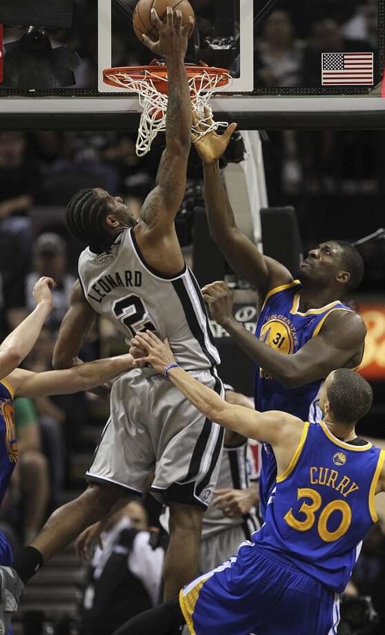 San Antonio Spurs' Kawhi Leonard scores over Golden State Warriors' Festus Ezeli during the second half of Game 2 in the NBA Western Conference semifinals at the AT&T Center, Wednesday, May 8, 2013. The Warriors won, 100-91 to even the series at 1-1.