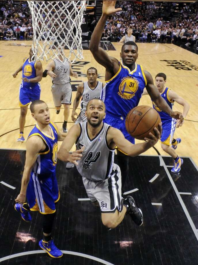 San Antonio Spurs' Tony Parker shoots between Golden State Warriors' Stephen Curry and Golden State Warriors' Festus Ezeli during first half action of Game 2 in the NBA Western Conference semifinals Wednesday May 8, 2013 at the AT&T Center. The Warriors won 100-91.