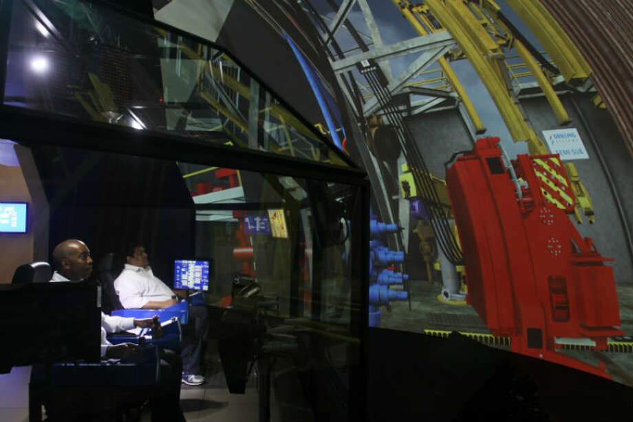 Diron Anderson, left, and Ernest Escalona using the Electronic Drilling Simulator at Diamond Offshore Drilling.