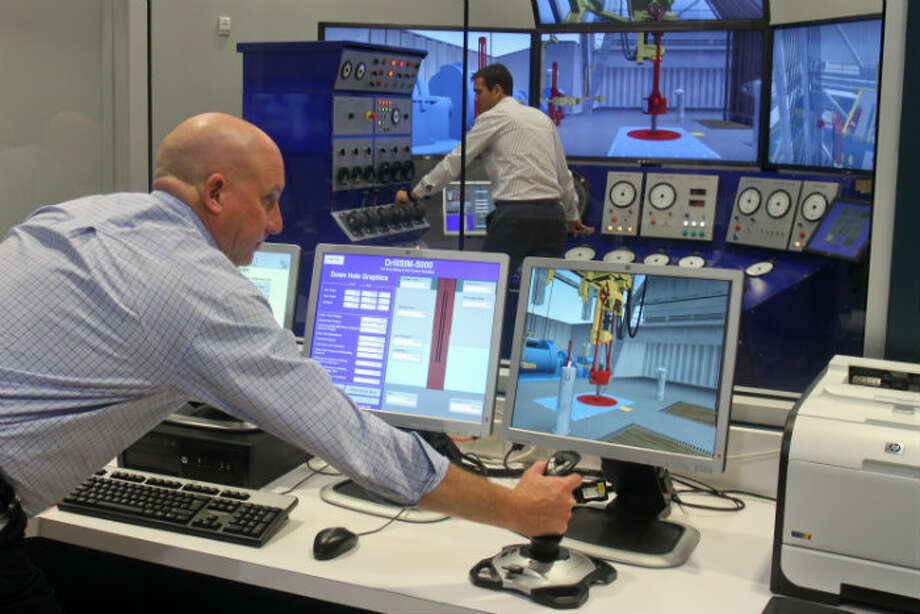 Brian Maness, front, and Petar Radulovic work in the reproduction of a drilling control room at Diamond Offshore Drilling's campus in Houston.