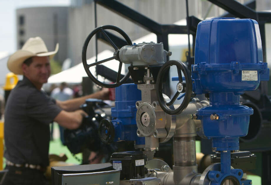A man leans on an ABZ Butterfly Valve & Actuator Tree during day three of the Offshore Technology Conference at Reliant Center Wednesday, May 8, 2013, in Houston. (Cody Duty / Houston Chronicle)