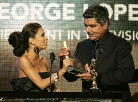 Host Eva Longoria gives a drum stick and cow bell to comedian George Lopez to play on stage after he accepted the 2007 ALMA award for special achievement in television at the taping of the National Council of La Raza's ALMA awards in Pasadena, California June 1, 2007. The show honors achievements by Latino artists in music, film and television and will be telecast in the U.S. June 5.   REUTERS/Fred Prouser   REUTERS/Fred Prouser        (UNITED STATES) Photo: FRED PROUSER, REUTERS / X00224