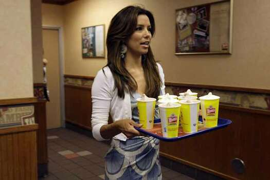 Actress Eva Longoria-Parker carries a tray full of Frosty servings at a Wendy's Restaurant in northeast San Antonio, Thursday, June 11, 2009. She was promoting the Dave Thomas Foundation for Adoption which kick's off the third annual Father's Day Frosty Weekend, June 20 and 21. Wendy's stores across the country will donate 50-cents of every Frosty sold to the foundation. It's goal is Ito raise $1.7 million. (AP Photo/San Antonio Express-News, Jerry Lara)** MAGS OUT, NO SALES, SAN ANTONIO OUT ** Photo: JERRY LARA, AP / SAN ANTONIO EXPRESS-NEWS
