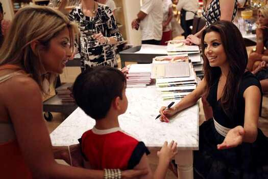 "Eva Longoria, right, greets customers at a signing event for her first cookbook, ""Eva's Kitchen: Cooking with Love for Family and Friends"", June 4, 2011, at Williams-Sonoma at the Shops at La Cantera. Only people with on of 400 tickets were allowed to get Longoria's signature in their books.   ANDREW BUCKLEY / abuckley@express-news.net Photo: ANDREW BUCKLEY, SAN ANTONIO EXPRESS-NEWS / SAN ANTONIO EXPRESS-NEWS"