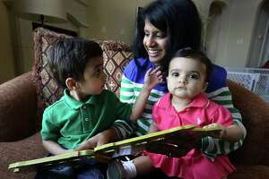 Nina Morgan reads to her 3 yr old son Luke as she holds her 11 mo old daughter Rachel in their home on Tuesday May 7, 2013.