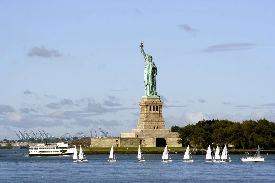 Sailboats, ferries and yachts at the foot of the Statue of Liberty