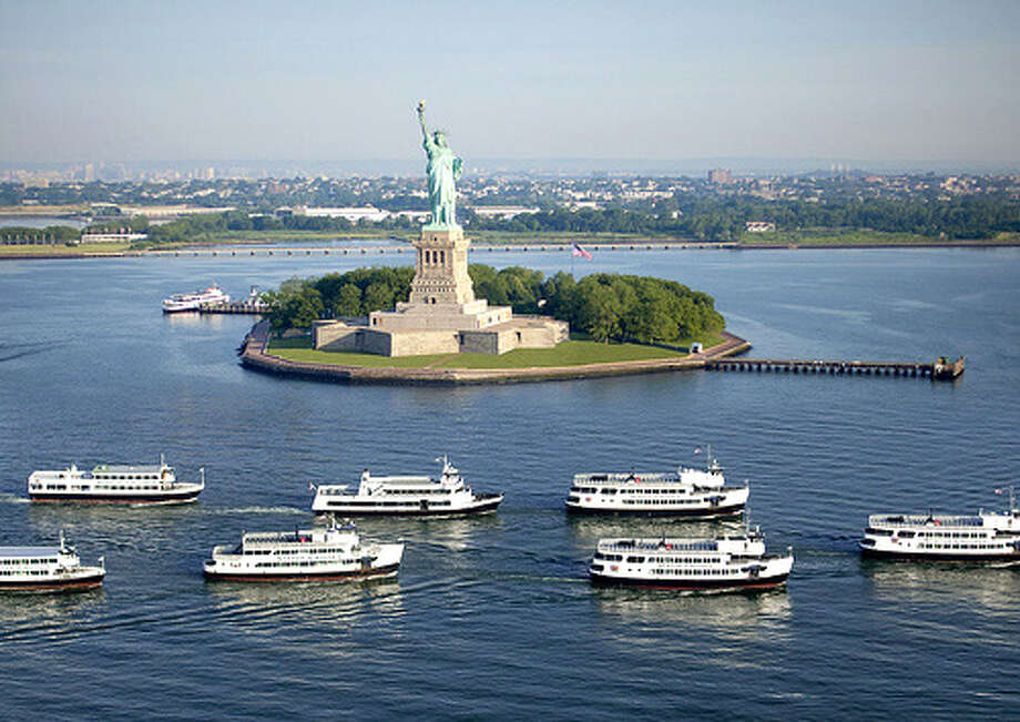 A fleet of ferries parades by Liberty Island.