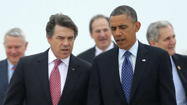In this May 9, 2013 file photo, President Barack Obama, right, talks with Texas Gov. Rick Perry, left, as the walk on the tarmac during his arrival on Air Force One at Austin-Bergstrom International Airport. Reversing his earlier stance, Obama has agreed to meet with Perry to discuss border security during a two-day visit to Texas that begins Wednesday. See more images from the crisis on the border. Photo: Pablo Martinez Monsivais, . / AP
