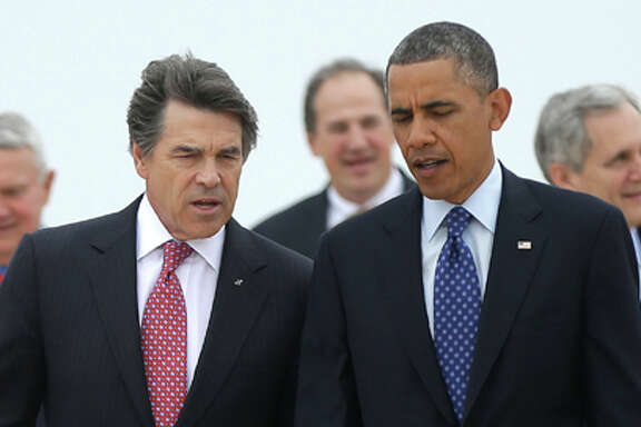 President Barack Obama, right, talks with Texas Gov. Rick Perry, left, as the walk on the tarmac during his arrival on Air Force One at Austin-Bergstrom International Airport, Thursday, May 9, 2013 in Austin, Texas.