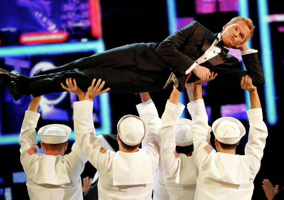 """FILE - This June 12, 2011 file photo shows host Neil Patrick Harris performing during the 65th annual Tony Awards in New York.  Harris will be back for his fourth turn as host of the Tony Awards. Producers of the show announced Thursday that Harris, a stage veteran and star of the CBS sitcom """"How I Met Your Mother,"""" will host the 67th annual awards to be presented June 9 at Radio City Music Hall in New York City. The show will air live on CBS. (AP Photo/Jeff Christensen, file) Photo: Jeff Christensen"""