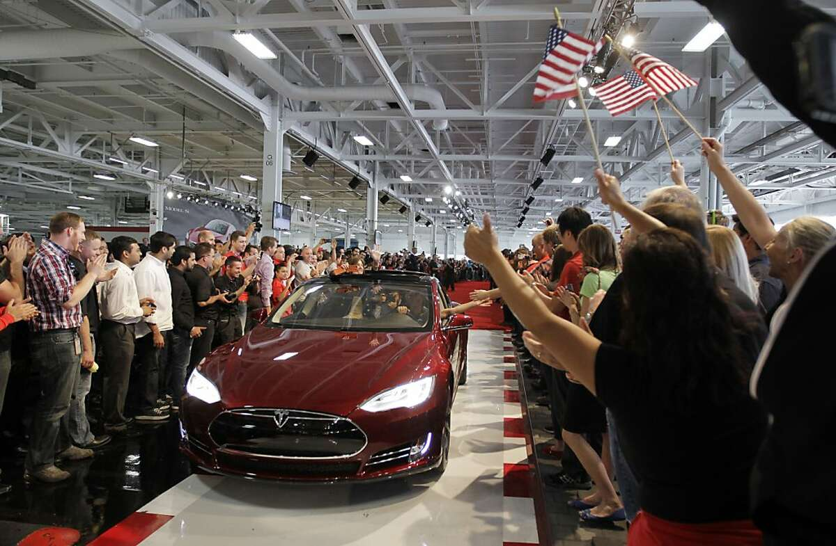 In this June 22, 2012 file photo, Tesla workers cheer on the first Tesla Model S cars sold during a rally at the Tesla factory in Fremont, Calif.