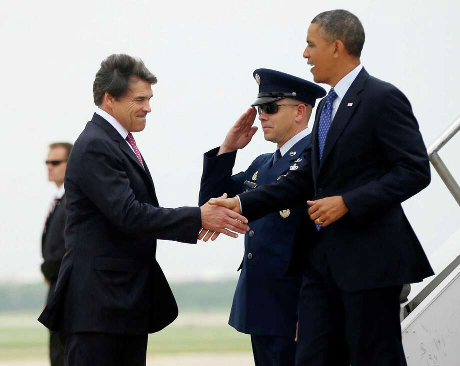 President Barack Obama, right, is greeted by Texas Gov. Rick Perry, left, during his arrival on Air Force One at Austin-Bergstrom International Airport, Thursday, May 9, 2013 in Austin, Texas. (AP Photo/Pablo Martinez Monsivais) Photo: Pablo Martinez Monsivais, Associated Press / AP