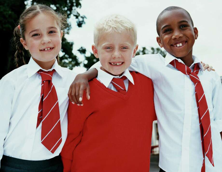 Portrait of Three Primary School Children Standing in a Line With Their Arms Around Each Other / (c) Digital Vision.