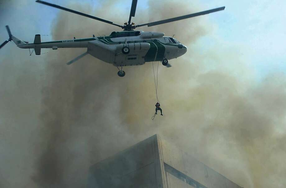 Saved from an inferno:A Pakistani army helicopter rescues a man from a burning building in Lahore. Five people plunged to their deaths while trying to escape the fire that engulfed the 13-story LDA plaza. Photo: Arif Ali, AFP/Getty Images