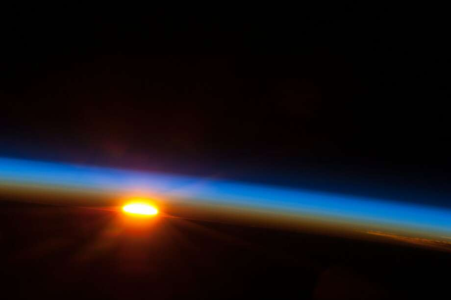 Rise and shine:The sun emerges from behind the Earth in the South Pacific Ocean in this image photographed by   one of the Expedition 35 crew members aboard the orbiting International Space Station. The space station was at   a point above Earth a few hundred miles east of Easter Island. Photo: Ho, AFP/Getty Images