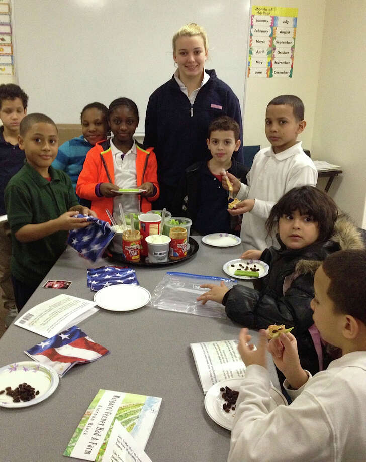 Girl Scout Kiernan Black gathers with students in one of her nutritious foods classes. For her community-service project to earn the Gold Scout Award, Black wrote a children's book about a woman who gathered fruits and vegetables for the needy, then Black launched an education program for kids and adults in Bridgeport. Photo: Contributed Photo / Fairfield Citizen contributed