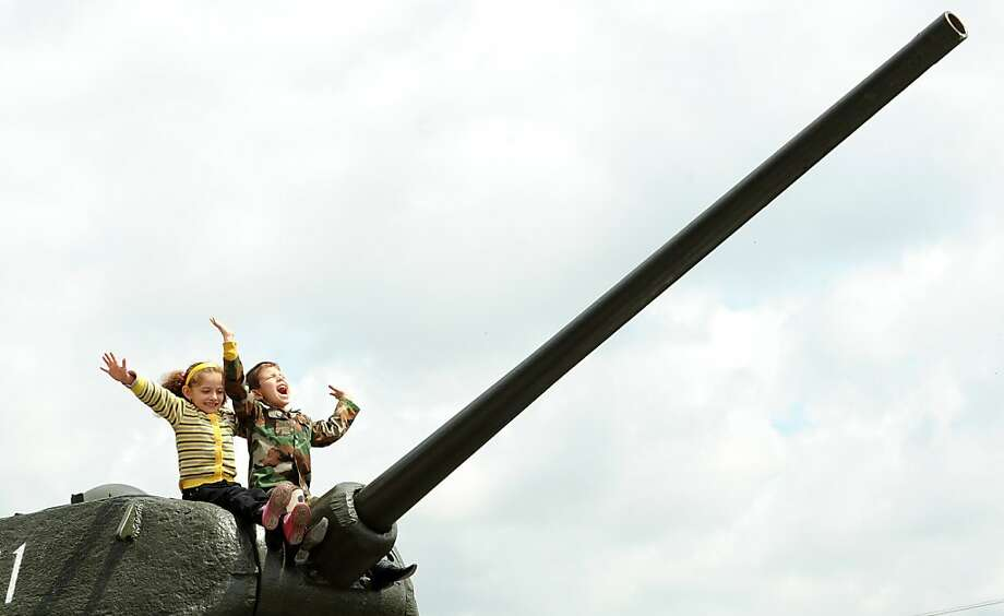 We sunk your battleship! Kids play on a  World War II-era Soviet T-34 tank during Victory Day celebrations in 