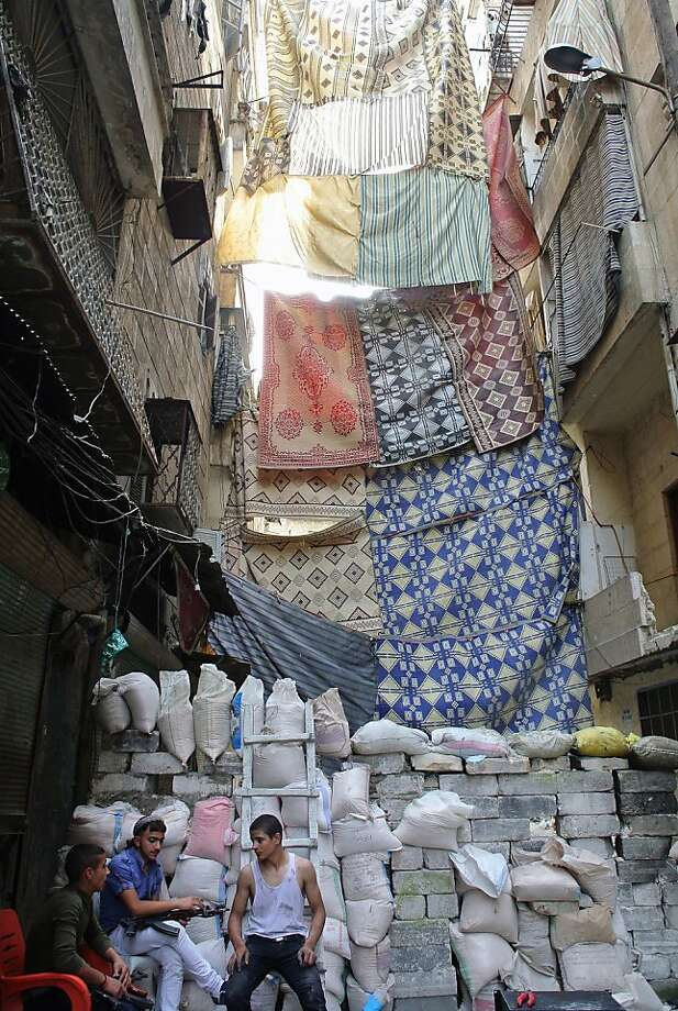 It's always laundry day in Aleppo:Linens and rugs are hung across a street in the Syrian city's Salaheddine district to block the sighting lanes of government snipers hoping to pick off Free Syrian Army fighters. Photo: -, AFP/Getty Images