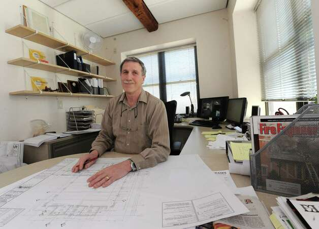Architect Robert Mitchell sits at his office desk in his converted 19th-century barn he restored to house his architect offices that is on the property next to the 1804 farmhouse he restored on Wednesday, April 17, 2013 in New Scotland, N.Y.  (Lori Van Buren / Times Union) Photo: Lori Van Buren