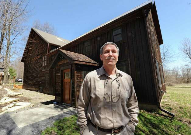 Architect Robert Mitchell stands outside his converted 19th-century barn he restored to house his architect offices that is on the property next to the 1804 farmhouse he restored on Wednesday, April 17, 2013 in New Scotland, N.Y.  (Lori Van Buren / Times Union) Photo: Lori Van Buren