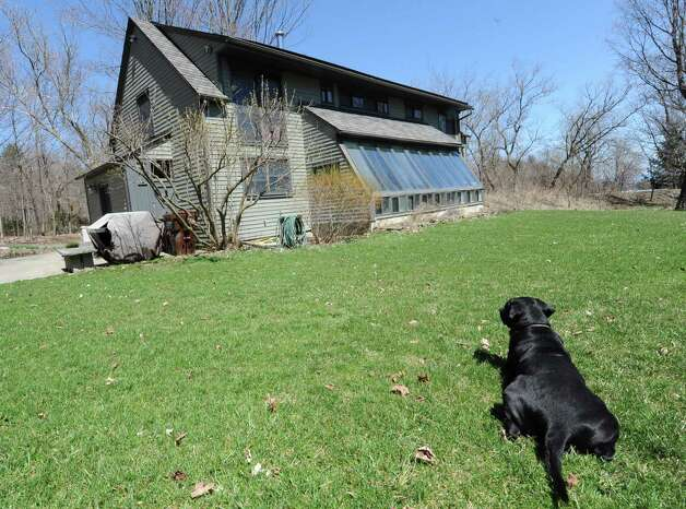 Architect Robert Mitchell's dog Oliver lays on the grass looking at his owners home which is a restored 1804 farmhouse on Wednesday, April 17, 2013 in New Scotland, N.Y.  (Lori Van Buren / Times Union) Photo: Lori Van Buren