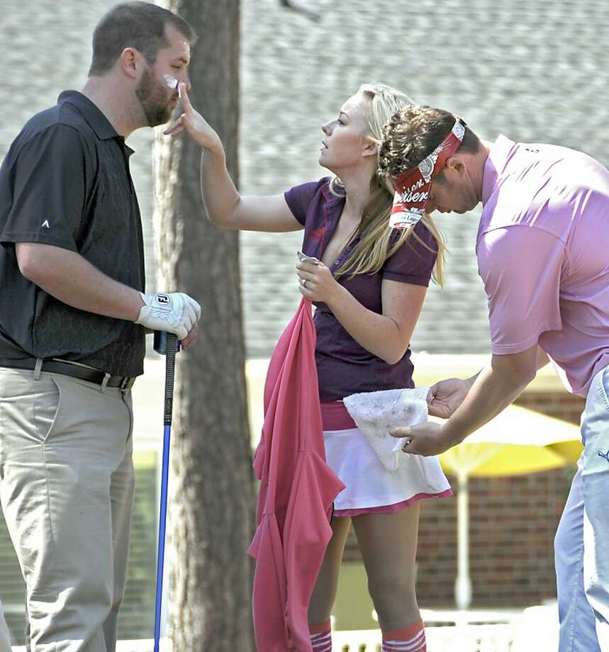 Sexy caddies are par for the course: Martin Hunt wipes his ball on Meghan Tarmey's towel, as Tarmey - the owner of The Caddy Girls at River Hills Golf and Country Club in Little River, S.C. - applies sunscreen to Asa Shirley. Tarmey's start-up business, which features female caddies in tiny skirts or short shorts, caters to golfers at courses in several states. Photo: Charles Slate, McClatchy-Tribune News Service