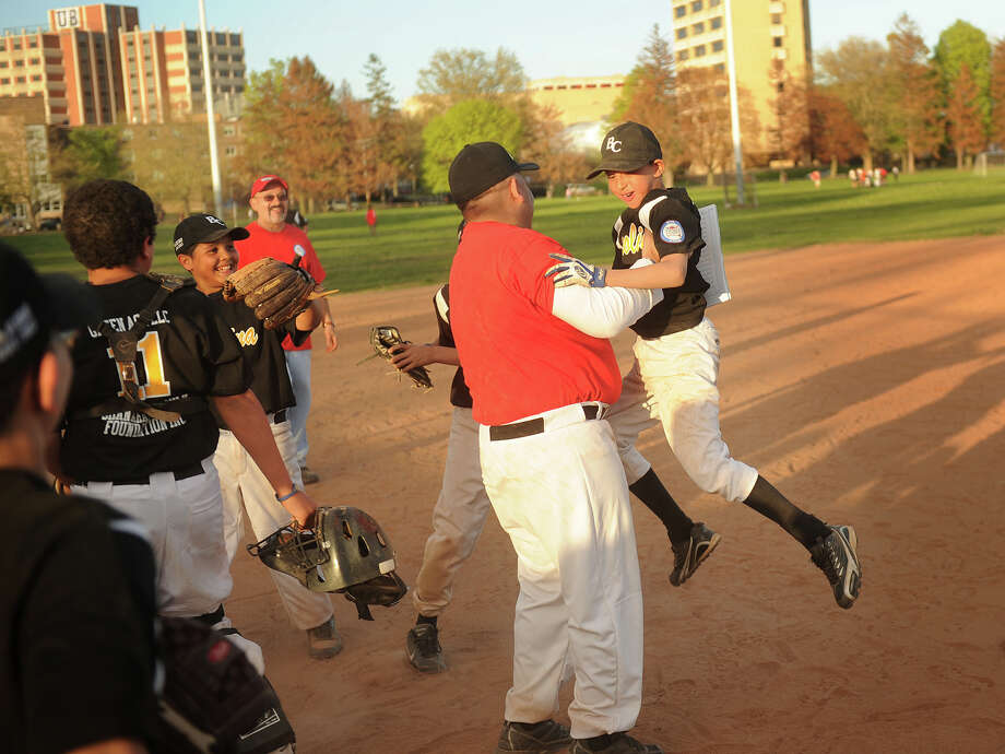 Gio Maisonet, 11, leaps into the arms of his coach, Steve Diaz, after winning a Caribe Youth Baseball League game at Seaside Park in Bridgeport, Conn. on Monday, May 6, 2013. Photo: Brian A. Pounds / Connecticut Post