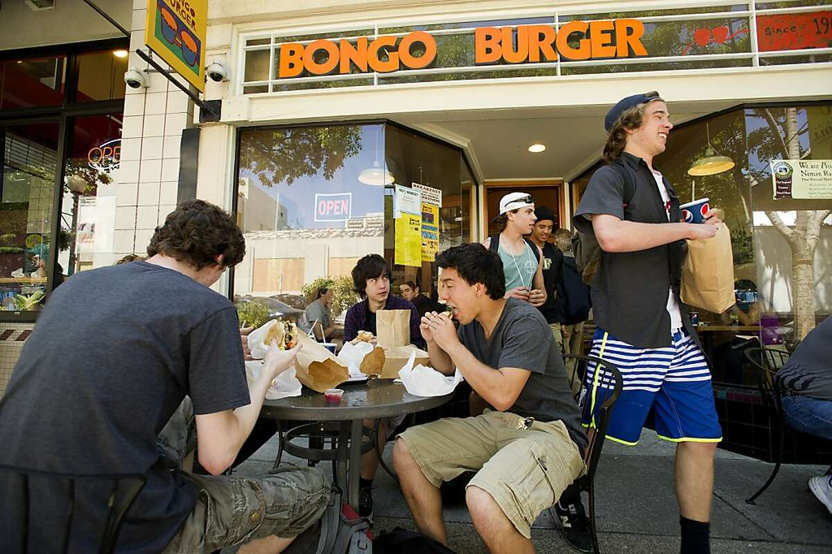 Scott Sowko, a sophomore at Berkeley High School, leaves Bongo Burger after lunching off-campus at Top Dog on Tuesday, April 30, 2013, in Berkeley, Calif. Seated at left are Berkeley High School seniors.
