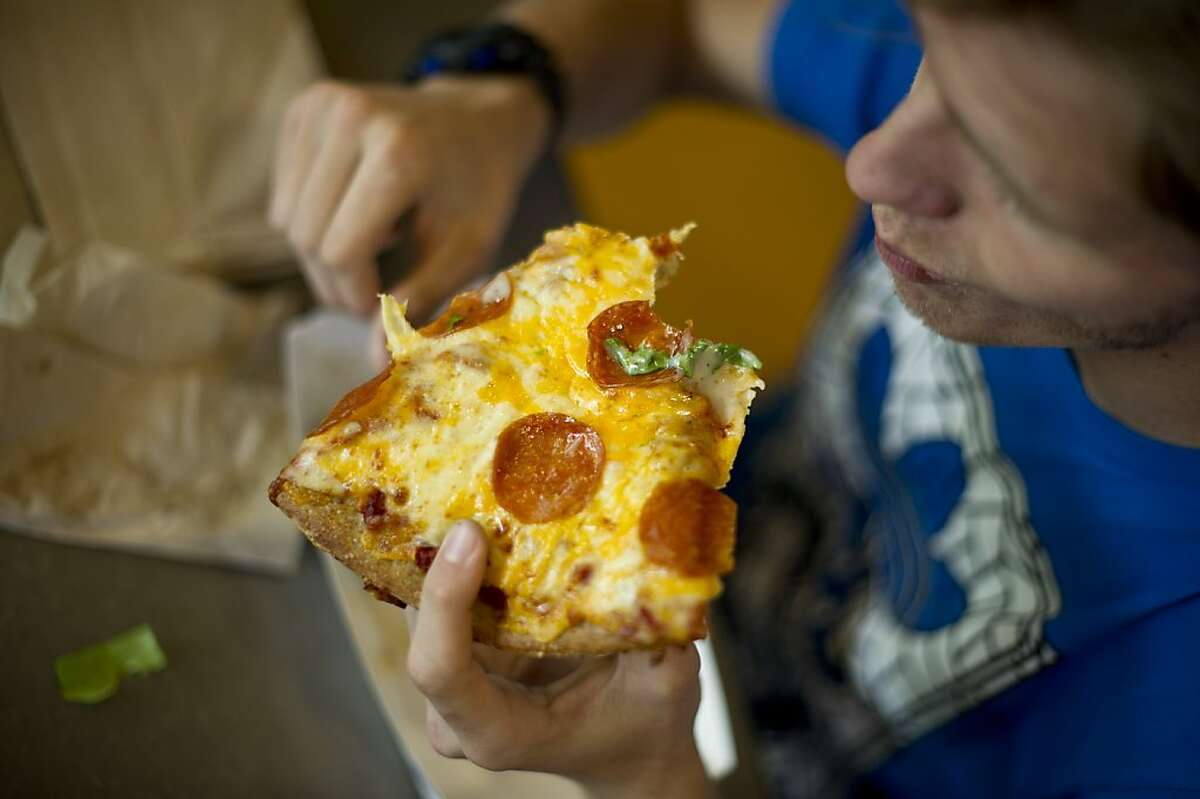David Smith, a senior at Berkeley High School, eats pizza in his school's cafeteria on Monday, April 29, 2013, in Berkeley, Calif.