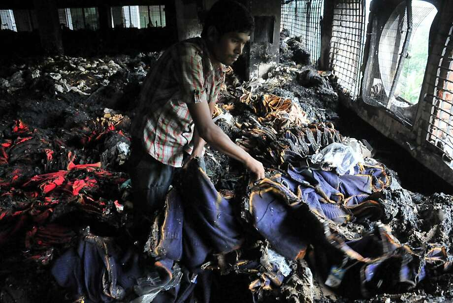 A worker inspects a burnt garment after a fire broke out at a garment factory building in Dhaka, Bangladesh, May 9, 2013. Shortly before midnight Wednesday, a fire swept through a garment factory in the capital Dhaka, killing eight people, including its managing director and a top police official. Initial reports suggested the fire in the 11-story building was caused by a short circuit on the second floor, which spread to the third and fourth floor where the factory was located. Photo: Shariful Islam/Xinhua, McClatchy-Tribune News Service