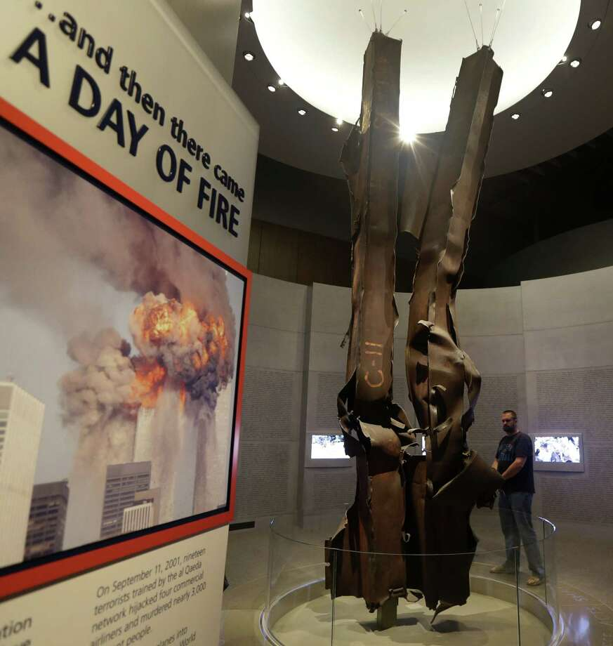 World Trade Center tower beams are shown on display as a visitor enters the 9/11 exhibit at the George W. Bush Presidential Library and Museum, on the campus of Southern Methodist University in Dallas. The statues (left) of George W. Bush and his father, George H.W. Bush, are next to Freedom Hall. Photo: Tony Gutierrez / Associated Press