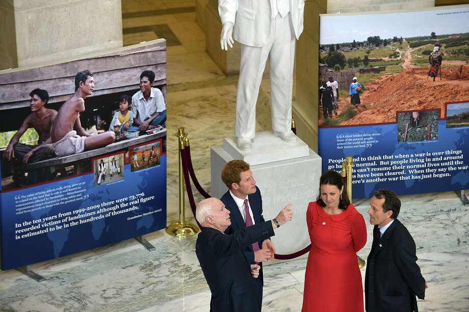 Britain's Prince Harry (2nd L) and US Senator John McCain (L) tour a land mine and unexploded ordnances exhibit on Capitol Hill on May 9, 2013 in Washington, DC. The exhibit of photos was put on by the HALO Trust. Photo: BRENDAN SMIALOWSKI, AFP/Getty Images / 2013 AFP