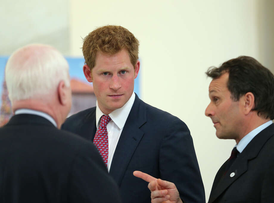 U.S. Sen. John McCain (R-AZ) (L) and HRH Prince Harry (C) tours an anti-landmine photography exhibition by The HALO Trust charity during the first day of his visit to the United States at the Russell Senate Office Building on May 9, 2013 in Washington, DC. HRH will be undertaking engagements on behalf of charities with which the Prince is closely associated on behalf also of HM Government, with a central theme of supporting injured service personnel from the UK and US forces. Photo: Chris Jackson, Getty Images / 2013 Getty Images