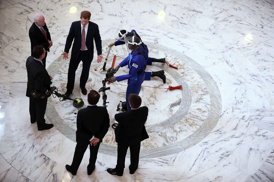 Prince Harry (2nd L) talks to mine detection demonstrators as he tours the HALO Trust exhibit on landmines and unexploded ordnances, escorted by U.S. Senator John McCain (L), inside the Rotunda of Russell Senate Office Building on Capitol Hill during the first day of his visit to the United States May 9, 2013 in Washington, DC. HRH will be undertaking engagements on behalf of charities with which the Prince is closely associated on behalf also of HM Government, with a central theme of supporting injured service personnel from the UK and US forces. Photo: Alex Wong, Getty Images / 2013 Getty Images