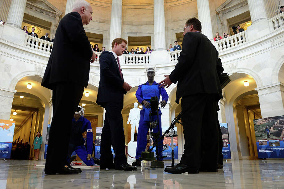 Prince Harry (2-L) is shown a ground penetrating radar, a tool used for detecting land mines, during tour of a HALO Trust photo exhibit on landmines and unexploded ordinances, with Republican Senator from Arizona John McCain (L) and HALO Trust Weapons and Ammunition Disposal Desk Officer Richard Boulter (R), on Capitol Hill on May 9, 2013 in Washington, DC. HRH will be undertaking engagements on behalf of charities with which the Prince is closely associated on behalf also of HM Government, with a central theme of supporting injured service personnel from the UK and US forces. Photo: Pool, Getty Images / 2013 Getty Images