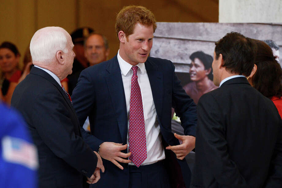 Prince Harry (2-L) tours a HALO Trust photo exhibit on landmines and unexploded ordinances, with Republican Senator from Arizona John McCain (L), Halo Trust Director Guy Willoughby (front R) and exhibit photographer Fiona Willoughby (back R), on Capitol Hill on May 9, 2013 in Washington, DC. HRH will be undertaking engagements on behalf of charities with which the Prince is closely associated on behalf also of HM Government, with a central theme of supporting injured service personnel from the UK and US forces. Photo: Pool, Getty Images / 2013 Getty Images
