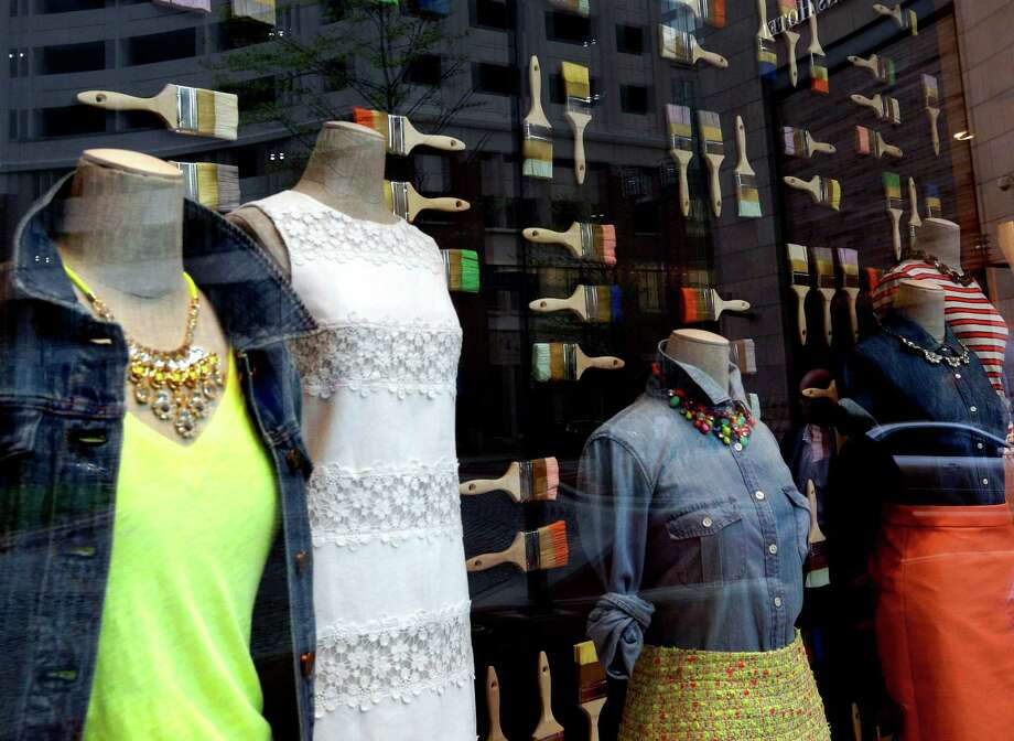 In this April 24, 2013 picture, clothing is modeled on mannequins in a retail store's window display in Baltimore. A report released May 9, 2013, showed Americans spent more during the early spring months as part the latest sign that they're encouraged by the economic recovery. Falling gas prices, a rallying stock market and gains in the job market all fueled Americans' shopping habits even as cold weather tempered their desire to buy spring fashions. (AP Photo/Patrick Semansky) Photo: Patrick Semansky