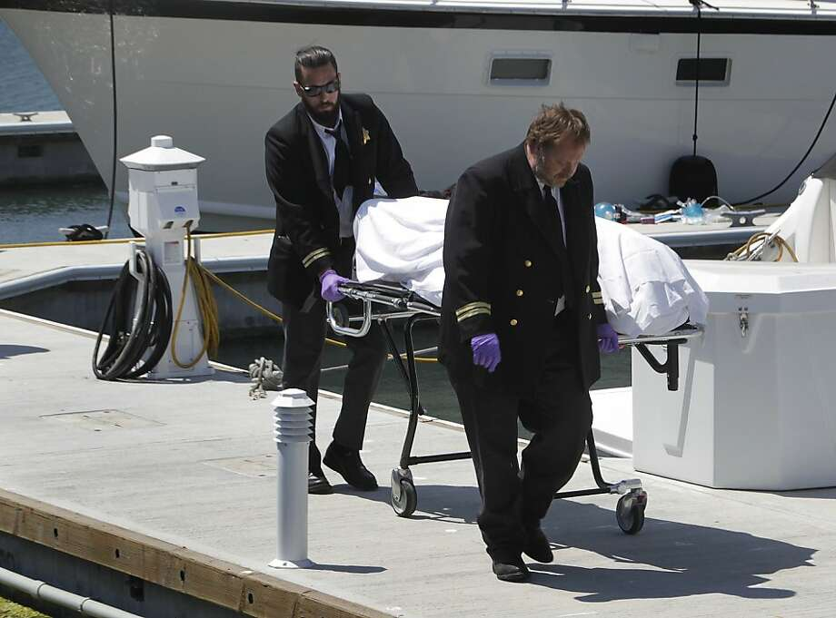 Medical examiners remove the body of a man from a Marina District dock who died after an Artemus team America's Cup racing boat apparently capsized, sending the entire crew into the bay in San Francisco, Calif. on Thursday, May 9, 2013. Photo: Paul Chinn, The Chronicle