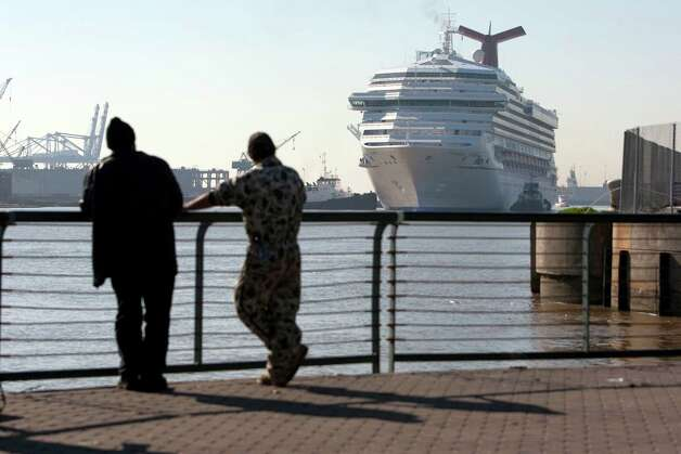 Richard Green, left, and Michael Cannon, of Mobile, looks on as the Carnival Triumph cruse ship is taken from the Alabama Cruise Terminal to be docked for repairs Friday, Feb. 15, 2013, in Mobile.  The vessel became stranded after an engine fire leaving the 4,000 passengers floating at sea. The ship was towed to Mobile by a group of tugboats. Photo: Johnny Hanson, Houston Chronicle / © 2013  Houston Chronicle