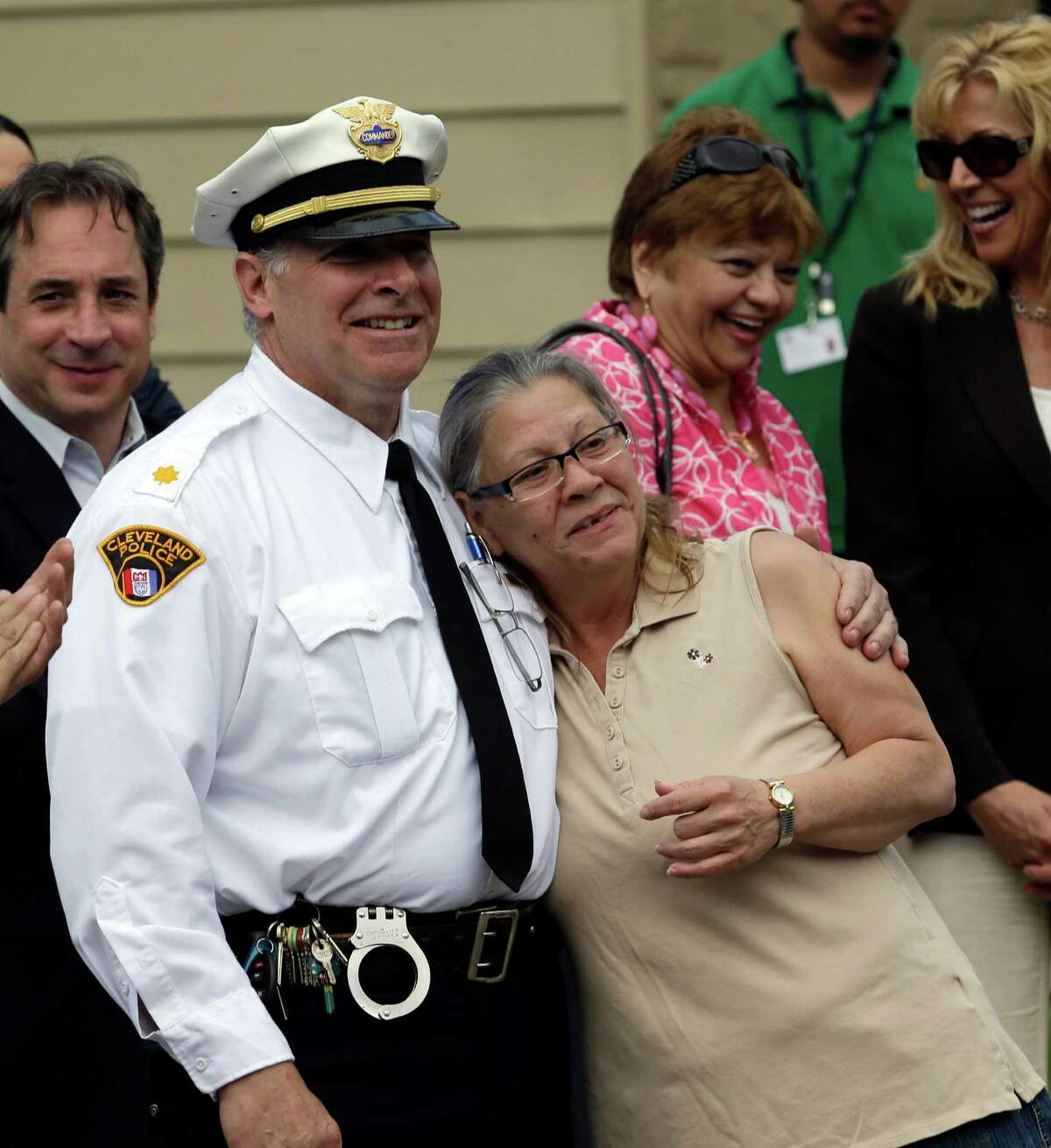 Commander K. Sultzer, left, hugs Nancy Ruiz, mother of Gina DeJesus, Wednesday, May 8, 2013, in Cleveland. DeJesus and two other women held captive for about a decade at a run-down Cleveland house were apparently bound with ropes and chains, police said Wednesday, while charges were expected by the end of the day against the three brothers under arrest.(AP Photo/Tony Dejak)