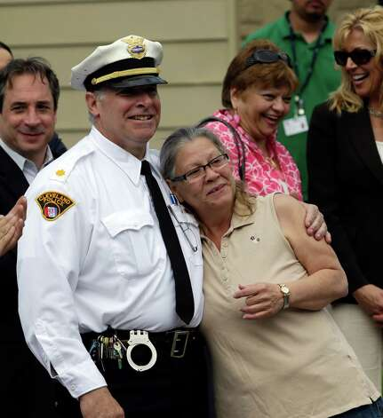 Commander K. Sultzer, left, hugs Nancy Ruiz, mother of Gina DeJesus, Wednesday, May 8, 2013, in Cleveland. DeJesus and two other women held captive for about a decade at a run-down Cleveland house were apparently bound with ropes and chains, police said Wednesday, while charges were expected by the end of the day against the three brothers under arrest.(AP Photo/Tony Dejak) Photo: Wire