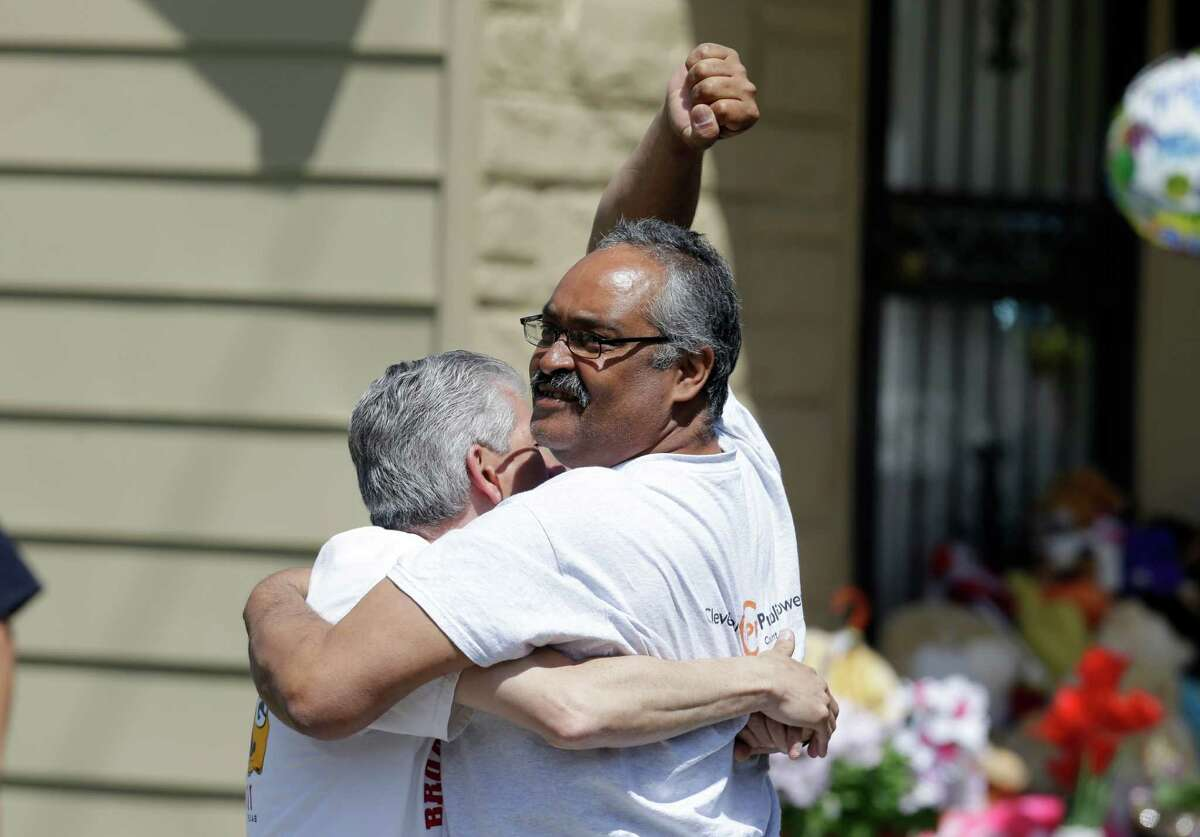 Felix DeJesus pumps his fist after bringing home his daughter, Gina, Wednesday, May 8, 2013, in Cleveland. The three women held captive for about a decade at a run-down Cleveland house were apparently bound with ropes and chains, police said Wednesday, while charges were expected by the end of the day against the three brothers under arrest. (AP Photo/Tony Dejak)