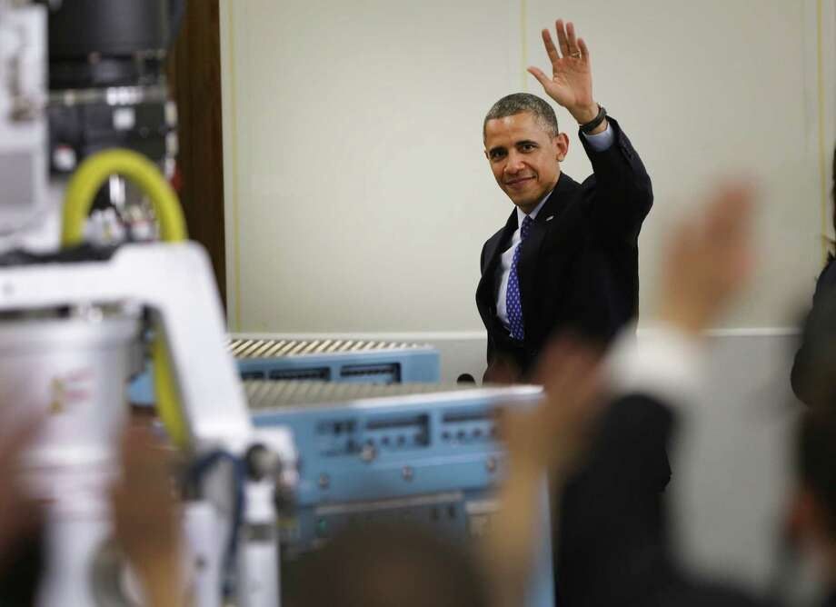 President Barack Obama waves, walking past high tech equipment made at Applied Materials, after speaking on Thursday May 9, 2013 at the Austin, TX company, stressing the importance of high technology education. Photo: Bob Owen, San Antonio Express-News / ©2013 San Antonio Express-News
