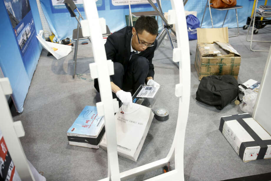 An OTC attendee packs up a exhibit booth on the final day of the conference. (Eric Kayne/For the Chronicle)